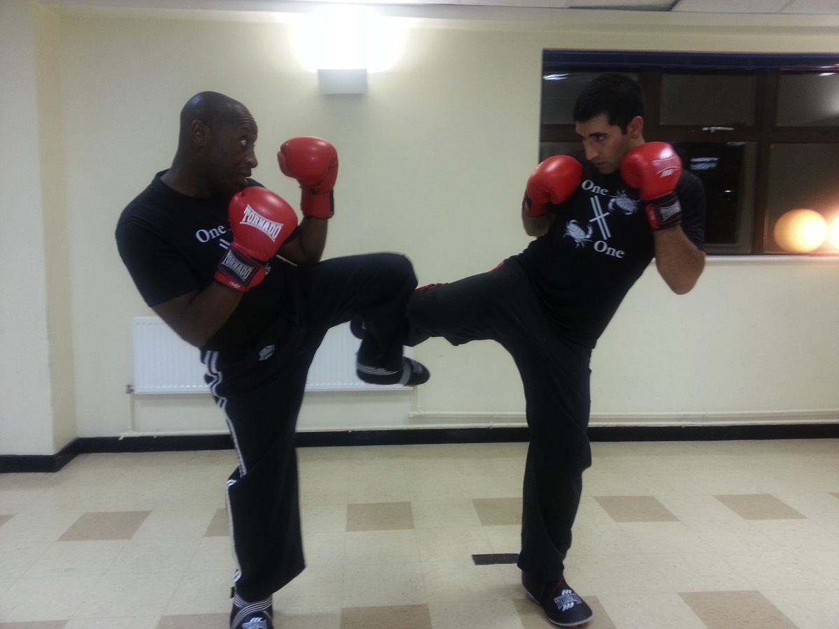 Rob and a Student pose for a kickboxing sparring session